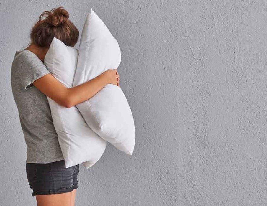 Девушка обнимает подушку