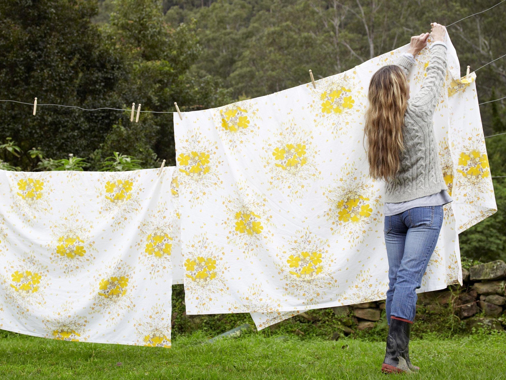 Женщина развешивает белье
