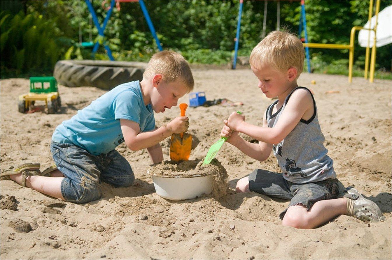 Мальчик с девочкой в песочнице играют