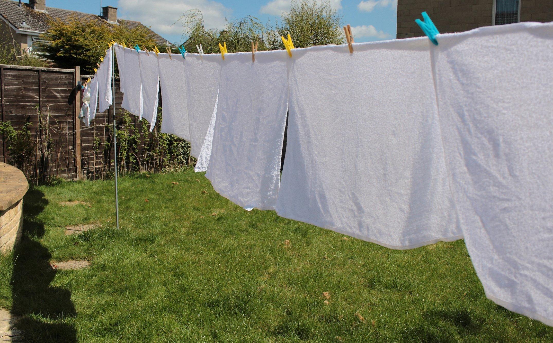 Белое полотенце сушится на веревке