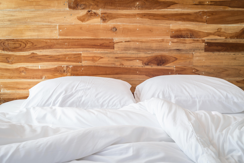 Кровать на фоне деревянной стены